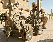 A U.S. Marine Corps technician prepares to deploy a device that will detonate a buried improvised explosive device near Camp Fallujah, Iraq.