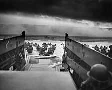 A black and white image of troops leaving an amphibious troop transport. They are walking through the water to a beach.