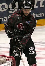 An ice hockey player standing directly in front of the camera. He is wearing a black helmet with a visor and a black and red uniform.