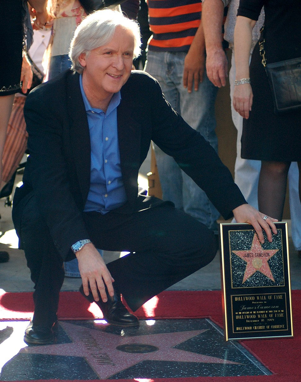 Director James Cameron squats by his new star, left hand propping up his plaque