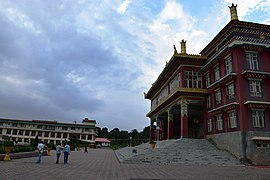 Three-story Tibetan-style building, with people outside for acale