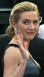 A young woman with blonde hair, pulled back from her face wears diamond earrings and grey formal gown. She looks to her right and waves and smiles.