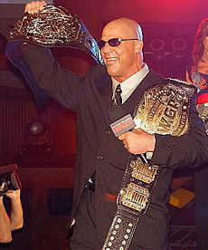Adult white male wearing a black suit and sunglasses holding two black belted championship belts and a microphone.