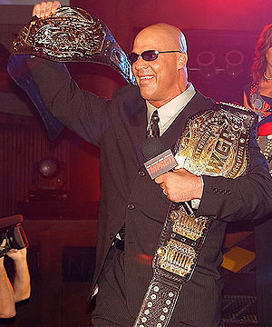 Impact Global Championship - Kurt Angle was the first TNA World Heavyweight Champion, seen here hoisting the first title belt design (left)