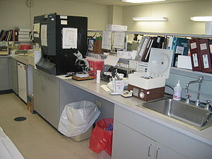 Medical laboratory - Laboratory equipment for hematology (black analyser) and urinalysis (left of the open centrifuge).