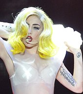 Gaga performing with her hands raised behind her neck. On the left biceps, a line of tattoos is visible.