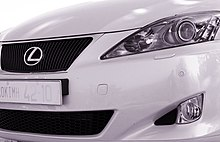 Car front fascia, partial view, with trapezoid grille, right headlight, and bumper.