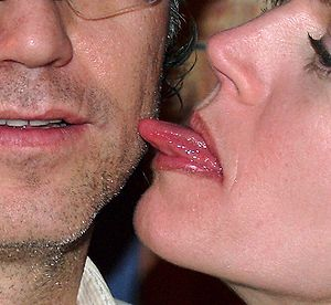 English: A woman licks a man's face.