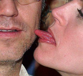 Licking - A woman licks a man's face.