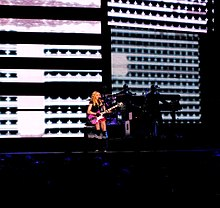 The picture is from a distance and shows a blond woman performing on a stage. She appears to wear red shorts and plays a pink guitar. Behind her, there are video screens showing horizontal graphical patterns
