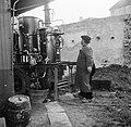 Man controleert de druk van de distilleerketel nadat hij kolen op het vuur heeft, Bestanddeelnr 252-9470.jpg