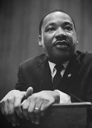 Martin Luther King leaning on a lectern.