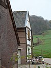 foto van Witgeverfde hoeve van baksteen, vakwerk en breuksteen. Onder een dak met buurnummer 6