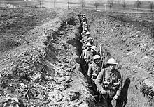 A file of soldiers from the King's Liverpool Regiment march down a shoulder-deep trench.
