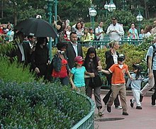 A man in public is dressed in black. He is surrounded by an entourage and members of the public, some of whom are holding cameras. He walks behind three young children, all of whom are wearing facial masks.