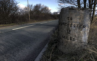 A57 road - A milestone along the A57, indicating the Warrington and Lower Irlam Turnpike Trust road, near Rixton. The opposite side gives the distance to Warrington.