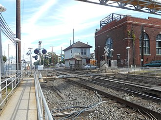 Mineola station (LIRR) - The Nassau Tower and substation in front of the pedestrian crossing.