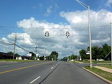 A four-lane highway proceeds into the background, where it disappears from view after descending a hill. Buildings home to various businesses, streetlights, and sidewalks line both sides of the highway. Two overhead signs held up by wires instruct drivers destined for NY 22B southbound to continue straight and those destined for NY 3 westbound to turn right ahead.