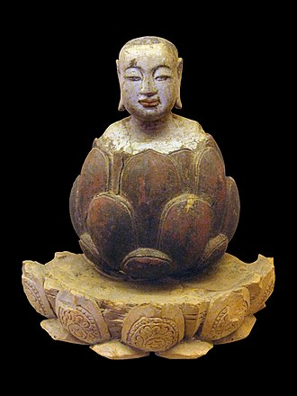 Lotus position - Buddha as a boy rising from a lotus flower. Crimson and gilded wood, Trần-Hồ dynasty, Vietnam, 14th-15th century
