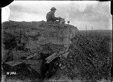 a man sitting atop a partially destroyed concrete bunker with a box in his hand.