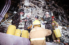 Several Air Force members and firefighters are clearing debris from the damaged building. Several yellow buckets are visible, which are being used to hold the debris, the destruction of the bombing is visible behind the rescuers.