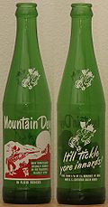 Two old green bottles of Mountain Dew. Left bottle is front cover; right bottle is back cover.