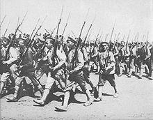 Duża grupa rosyjskich żołnierzy w jasnych koszulach mundurowych i czapkach sukiennych maszeruje w prawą stronę kadru, w niezorganizowanej grupie. Wszyscy uzbrojeni są w karabiny Mosina.
