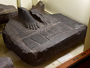 Hotep - Part of base of basalt royal statue. Queen's feet on 9 bows before an offering table. Hotep sign at front edge. Hes vase with spouted vases and lamp. Late Period. From Egypt. The Petrie Museum of Egyptian Archaeology, London