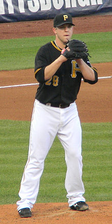 A man in a black baseball jersey, white pants, and black baseball cap wearing a black baseball glove on his right hand preparing to pitch from a baseball mound.