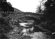 Black and white photograph of the side of a stone bridge arching over a shallow rocky stream. The torso and head of a person wearing a hard hat can be seen on the left side of the bridge.