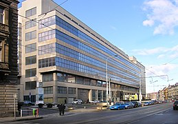 Imposante façade de béton et de verre, à dominante grise, donnant sur une rue importante.