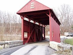 Interior structure of a covered bridge utilizing a queen-post structure
