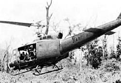 Black and white photograph of a helicopter flying at a low altitude