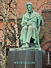 "A statue. The figure is depicted as sitting and writing, with a book on his lap open. Trees and red tiled roof is in background, the statue itself is mostly green, with streaks of grey showing wear and tear. The statue's base is grey and reads ""SØREN KIERKEGAARD"""