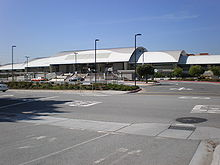 A train station with white roof situates behind an empty parking lot and road