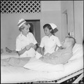 Saigon, South Vietnam....Lieutenant Frances Crumpton and Miss Nangnoi Tongkim, a Thai nurse, talk with an American... - NARA - 558528.tif