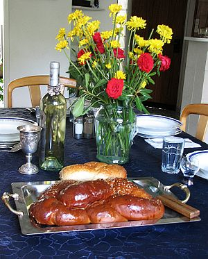 English: Table set for Shabbat with challah an...
