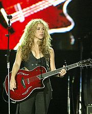 A woman standing behind a microphone, holding an electric guitar.