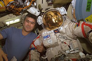 Salizhan Sharipov - Salizhan Sharipov, Expedition 10 flight engineer poses with his Orlan spacesuit in the Pirs Docking Compartment of the ISS.