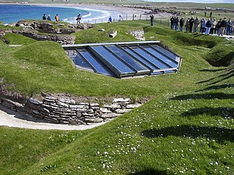 Skara Brae - View over the settlement, showing covering to house No. 7 and proximity to modern shore line. The glass roof has now been replaced by a turf one, as the humidity and heat caused by the glass roof was hindering preservation.