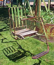 A metal chair, painted green, with footrest and wooden seat suspended above a grassy area by a metal pole on the right side