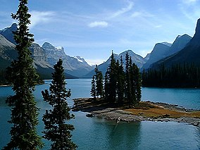 A small island with spruce trees on an alpine lake surrounded by peaks