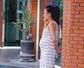 Standing pregnant woman with her mobilphone.jpg