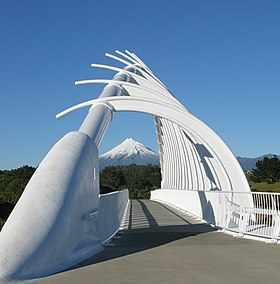 View through the steel arch of a bridge, with a mountain in the background