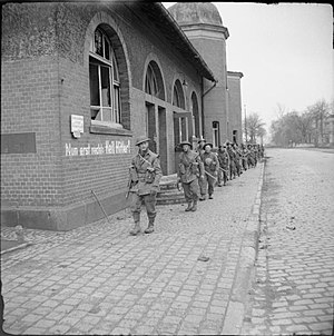 160th Infantry Brigade and Headquarters Wales - Men of the 2nd Battalion, Monmouthshire Regiment in Bocholt, Germany, 29 March 1945. Note the Nazi slogan painted on the wall.