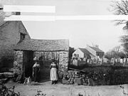 women in traditional dress at church gate with church and graveyard in background in 1885