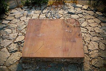 Photo en couleur d'une pierre rectangulaire déposée sur un sol en pierres et comportant une inscription en grec