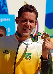 Brazilian athlete poses for photographs after the awards ceremony of the men's 200 metre individual medley competition. Wearing the official uniform of the Brazilian delegation, he holds the gold medal with his left hand.