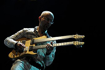 Timuçin Şahin performing with a double neck fretless and fretted guitar.