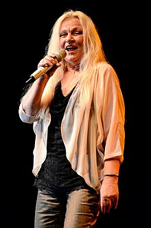 Colored photograph of Toni Willé standing onstage holding a mike. She has long blonde hair and is wearing a black top and off-white full-sleeved top with grey pants.